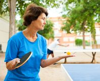 Elderly woman starts a party in table tennis. Elderly women starts a party in table tennis at outdoor royalty free stock photos
