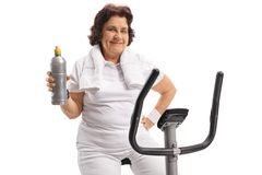 Elderly woman on a stationary bike holding a water bottle. Isolated on white background Stock Photos