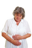 Elderly woman with stomach cramps Royalty Free Stock Photography