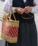 Elderly woman with straw bag walking Royalty Free Stock Image