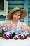 Elderly woman in straw hat with jars Stock Images