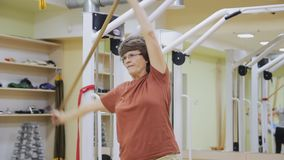 Elderly woman stretching out, doing tilt exercises with stick in fitness room. Healthy gymnastics. Active seniors. stock video