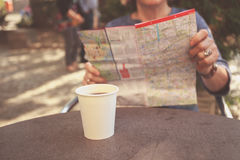 Elderly woman studying map and having coffee Stock Photography