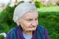 Elderly woman suffering from dementia. Close up portrait of smiling elderly woman suffering from dementia disease, outdoor stock photos