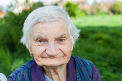 Elderly woman suffering from dementia. Close up portrait of smiling elderly woman suffering from dementia disease, outdoor stock photo