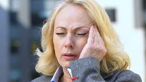 Elderly woman suffering migraine after intensive working day, stressful job. Stock footage stock video
