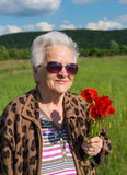 Elderly woman in sunglasses with bunch of poppies Royalty Free Stock Photos