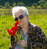 Elderly woman in sunglasses with bunch of poppies Royalty Free Stock Photo