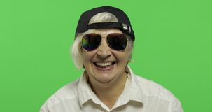 An elderly woman in sunglasses and cap smiles. Old grandmother. Chroma key. An elderly woman in sunglasses and cap smiles. Laughing. Old pretty happy grandmother stock video