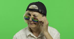 An elderly woman in sunglasses and cap smiles. Old grandmother. Chroma key. An elderly woman in sunglasses and cap smiles. Old pretty happy grandmother in a stock footage