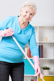 Elderly woman sweeping floor Stock Photography