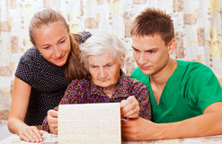 Elderly woman with the sweet young doctors stock photo