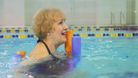 Elderly woman swims in pool. Elderly woman swims in the gym with noodle. Old woman has a healthy lifestyle and spend her leisure time in swimming pool stock video footage