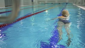 Elderly woman swims in the pool. Elderly woman swims in the swimming pool. Senior woman has a healthy lifestyle and spend her leisure time swimming in the water stock video footage