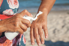 Elderly woman in swimsuit using cream for hand on beach Royalty Free Stock Images