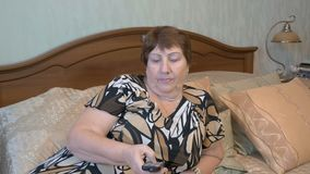 Elderly woman switches channels TV remote. 4K stock video footage