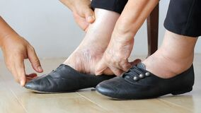Elderly woman swollen feet putting on shoes with care giver