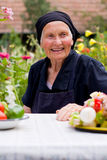 Elderly woman at the table. An elderly woman sitting at the table with healthy food in front of her, laughing royalty free stock photos