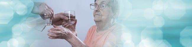 Elderly woman taking medication. panoramic banner royalty free stock photography