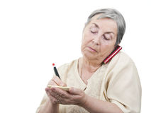 Elderly woman taking notes at cellphone Stock Photography