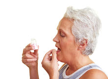 Elderly woman taking a pill Royalty Free Stock Photography