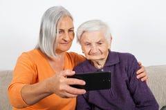 Elderly women`s selfie. Elderly women taking a selfie with smiling caregiver stock photo