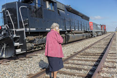 Elderly woman talking on the cell phone. Elderly woman standing on the railroad track talking on a cell phone Royalty Free Stock Photo