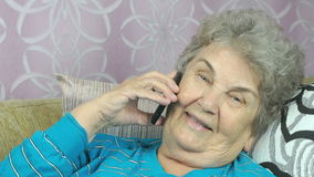 Elderly woman talking with friend on mobile phone stock video footage
