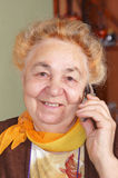 Elderly woman is talking by a mobile Royalty Free Stock Photography