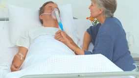 Elderly woman talking to her unconscious husband. At the hospital stock footage