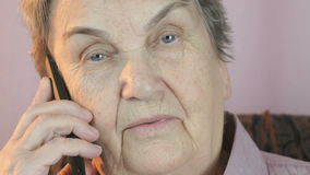 Elderly woman talks on smartphone with smile stock video footage