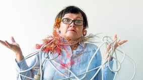 An elderly woman is tangled in wires. stock image
