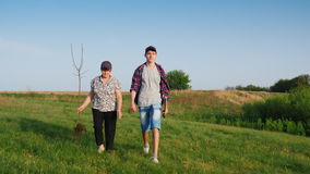 An elderly woman with a teenage grandson is going to plant a tree. They carry in their hands garden tools and a tree stock video footage