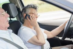 Elderly woman on telephone while driving car Stock Photo