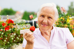 Elderly woman on the terrace. Elderly smiling woman sitting on the terrace, holding a strawberry Stock Photo