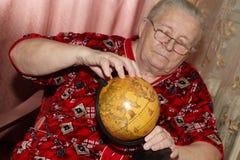 Elderly woman and terrestrial globe Stock Photo