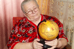 Elderly woman and terrestrial globe Royalty Free Stock Images