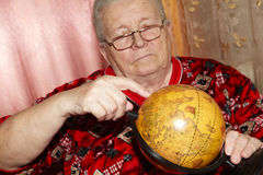 Elderly woman and terrestrial globe Royalty Free Stock Image