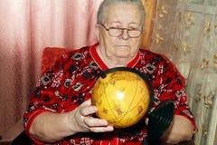 Elderly woman and terrestrial globe Royalty Free Stock Photos