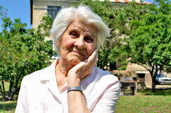 An elderly woman, thought. An elderly woman, lost in thought, leaning on the arm, von Garden Stock Photos