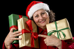 Elderly Woman with Three Wrapped Christmas Gifts. Female senior hugging three wrapped Christmas presents, while pointing her left index finger at two of them Stock Photos