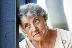 Elderly woman tired and sad face. On a light grey background royalty free stock photo