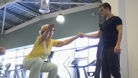 Elderly woman trains with coach in the gym. Trainer in the gym helps granny to squat at balance platform. Elderly woman training in the gym with coach stock footage