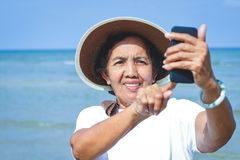 Elderly women holding phones to take pictures stock photos
