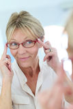 Elderly woman trying on eyeglasses at optical store Stock Image