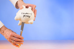 Elderly woman trying to squeeze money out of piggybank Royalty Free Stock Photos