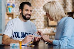 Elderly woman trying to use a convenient pill box. So easy. Cheerful curious pensioner trying to use a new convenient pill box while a happy volunteer helping Stock Photography