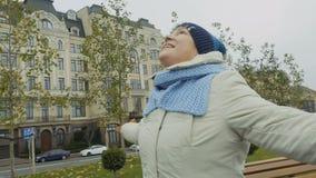 Elderly woman turning around herself walking in park. Happy elderly woman is whirling walking in park. Cheerful grandmother is turning around happily feels stock footage