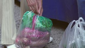 Elderly Woman Tying Plastic Bags Together