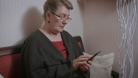 Elderly woman typing on the smartphone. stock footage